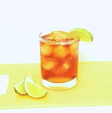 Gosling's Dark and Stormy Cocktail in a rocks glass on a yellow cutting board with limes