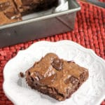 closeup of chewy fudge brownies from scratch on a red table