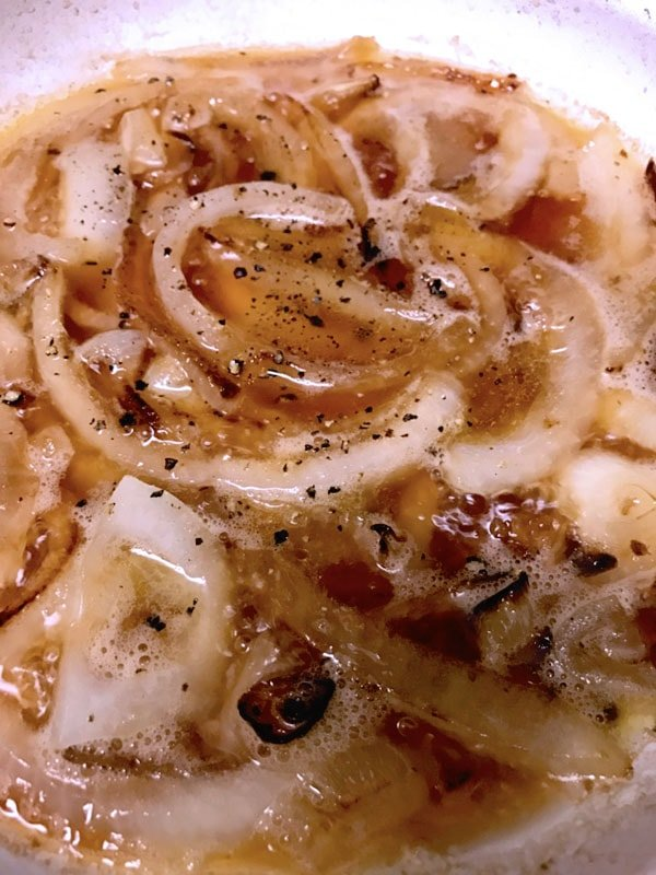 Sliced onions caramelized with beer on white plate
