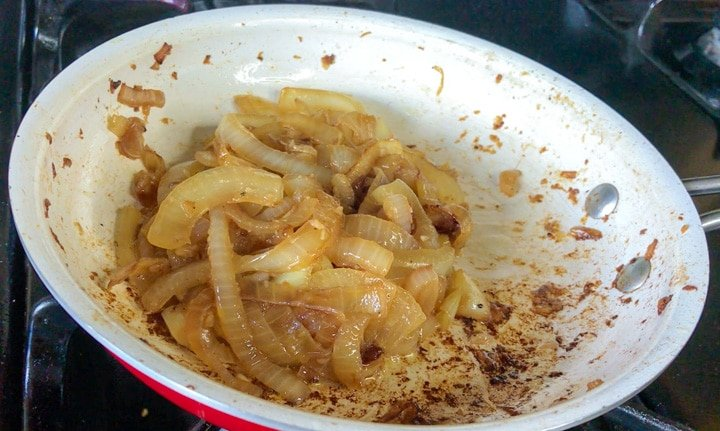 Sliced onions caramelized with beer in white bowl