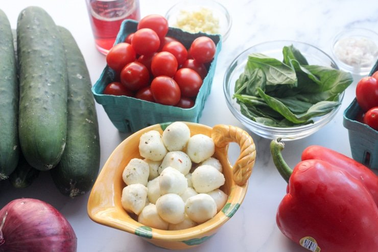 ingredients for caprese cucumber salad in small bowls