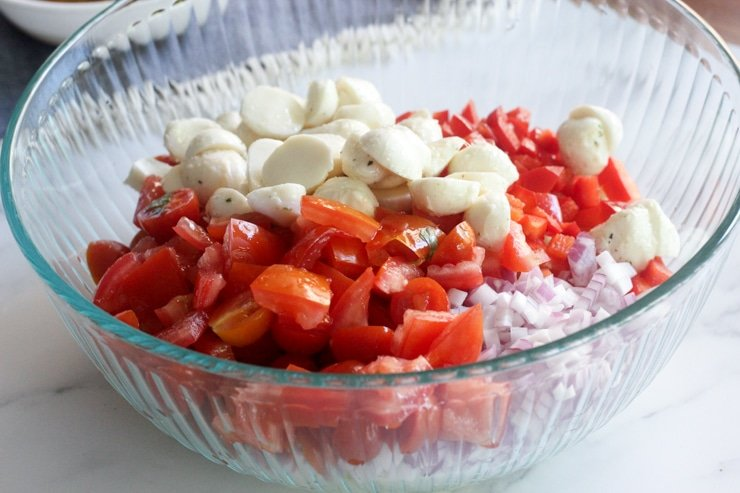 diced tomato, cucumber, red pepper and onion, with mozzarella balls in a mixing bowl