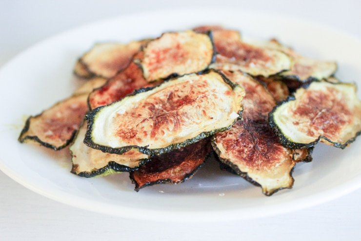 thinly sliced oven baked zucchini chips using a mandolin on a white kitchen counter