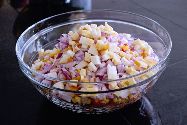 chopped cheese, onions, corn and other ingredients for Mexican salad in glass bowl