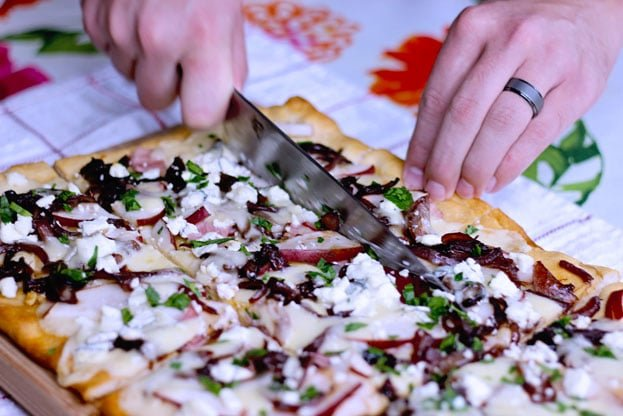 cutting pizza on a cutting board featuring pear and goat cheese flatbread topped with caramelized onions, ham and cheddar