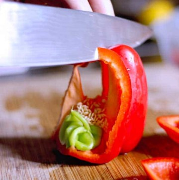 Cutting A RED PEPPER into strips upside down on a cutting board