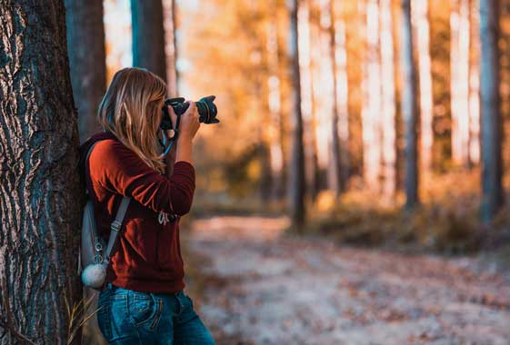 roadtrip in the fall in oregon woman taking photos in the woods while hiking