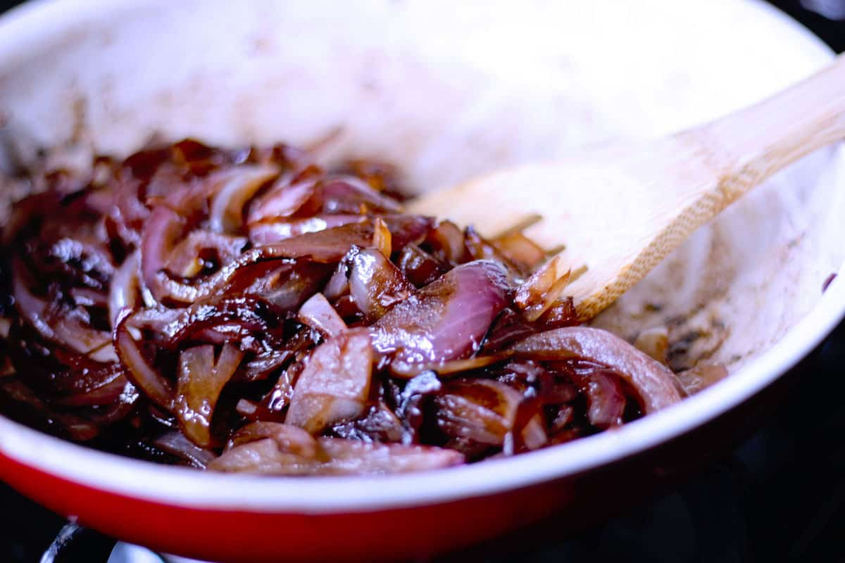 Side shot of red onions caramelized in a white pan on the stove.