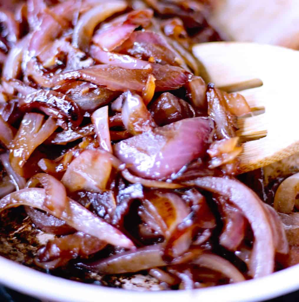 Side shot of sauteed onions in a pan with a spatula.