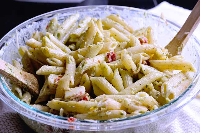 combining creamy pesto pasta salad with mozzarella, sun-dried tomatoes and with store bought pesto