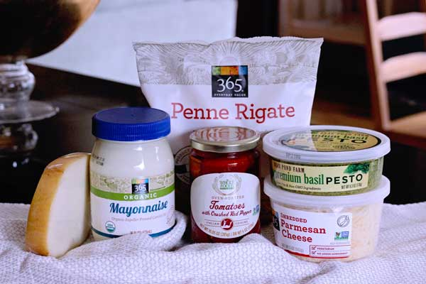 ingredients for creamy pesto pasta salad with with store bought pesto including tomatoes, mozzarella, pesto, mayo, penne pasta, parmesan cheese