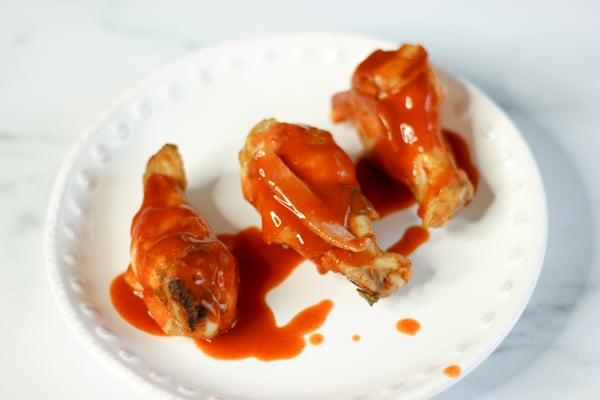 Sous vide wings with Franks buffalo sauce on a white plate