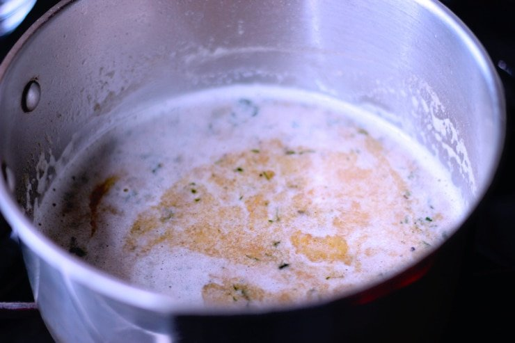 top shot of IPA beer mixed with roux and seasonings in a large pot on the stove