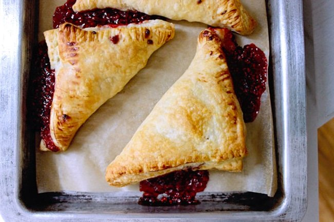 Top shot of freshly baked raspberry puff pastry turnovers baked in the oven on a sheet pan.