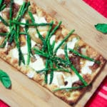 cutting board with basil and asparagus pizza with pesto, mozzarella, and caramelized onions