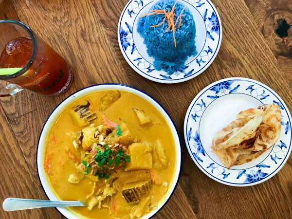 Thai Farmhouse Kitchen lunch menu items yellow curry with potato, onion, crispy shallot and chicken with a side of roti andblue rice