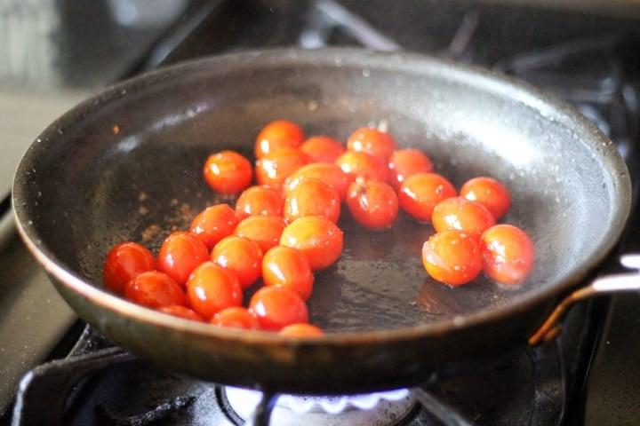 Cherry tomatoes roasting on medium heat on the stove