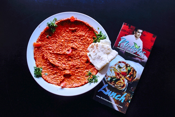 roasted red pepper and walnut hummus on a plate with pita bread and a nicholas restaurant menu