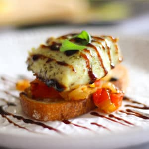 baked barramundi fish toast appetizer with red pepper and corn salsa topped with basil and balsamic glaze