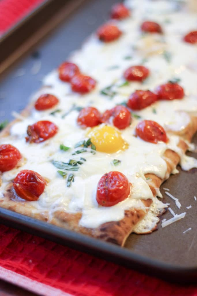 cooked breakfast pizza with eggs and tomatoes on a rimmed baking sheet