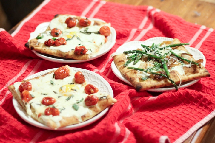 slices of breakfast pizza with eggs and asparagus pizza on a red kitchen cloth
