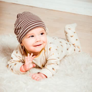 Baby sleeping in a long sleeve footed pajama and a hat for the winter