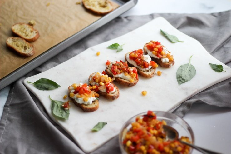 ricotta crostini topped with roasted red pepper salsa on a party tray