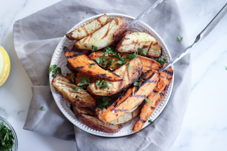 grilled sweet potatoes on a white plate and kitchen towel
