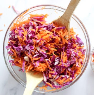 shredded carrots and shredded red cabbage with a no vinegar dressing in a glass bowl with wood spoons