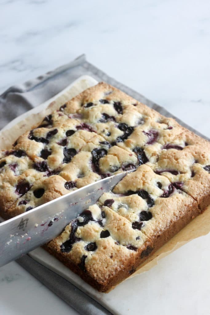 slicing mixed berry dessert into cake bars
