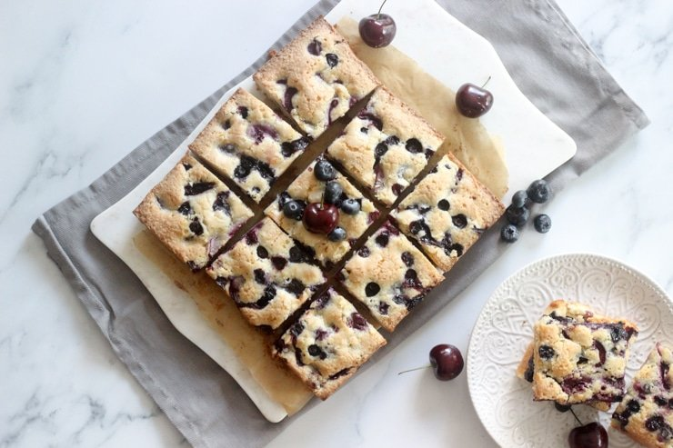 fresh blueberry and cherry cake bars on a table ready to serve