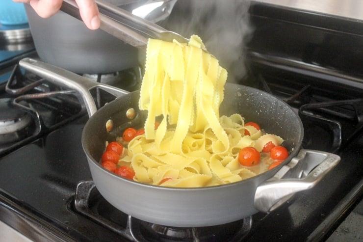 adding pasta to chicken piccata