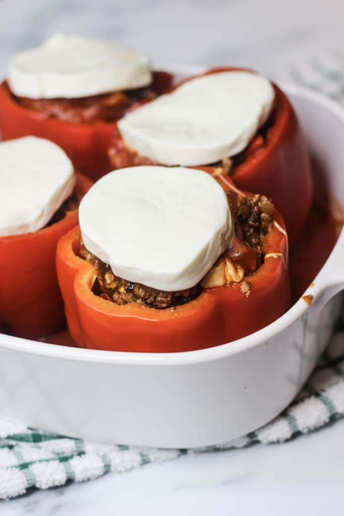 slices of mozzarella on top of Italian stuffed peppers