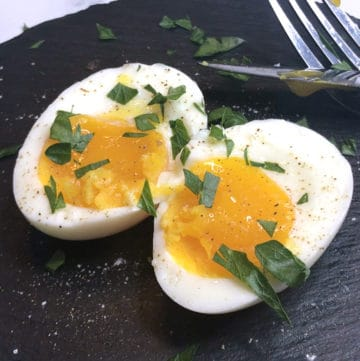 sous vide soft boiled eggs cut in half with salt and herbs