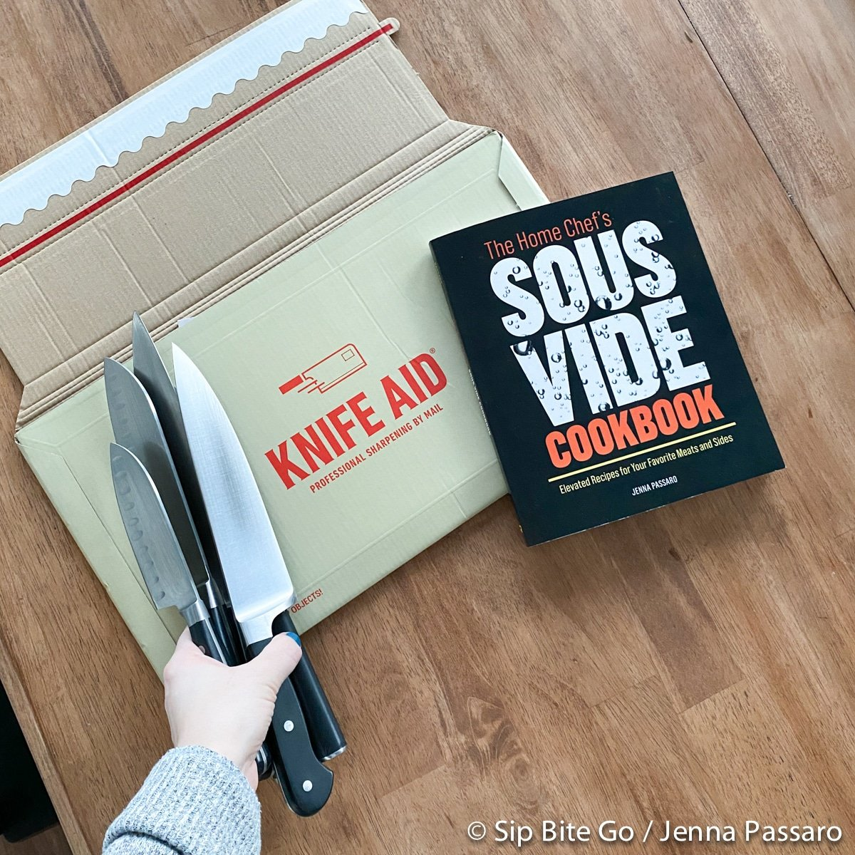 Knife AId box with knives in hand ready to be sharpened with the home chef's sous vide cookbook