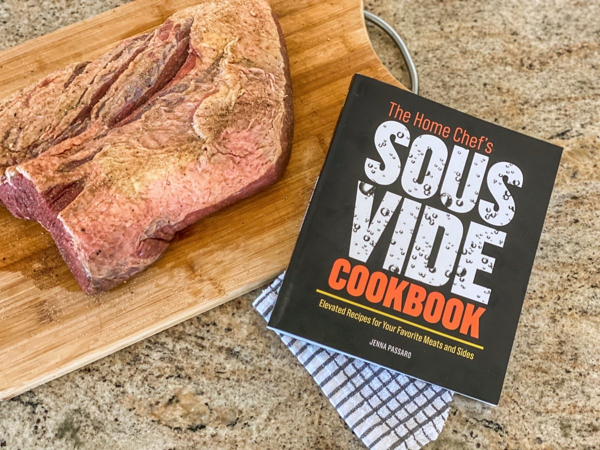 sous vide beef on a cutting board with the sous vide cookbook by Jenna Passaro