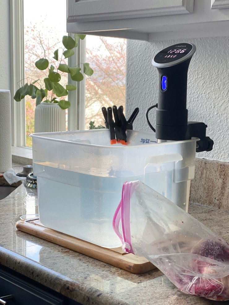 setting up sous vide cooking recipe with a container of water and a sous vide machine