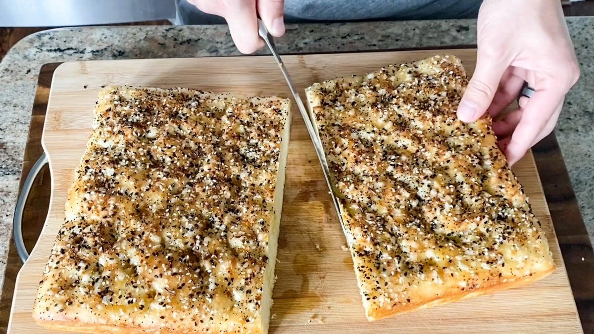 slicing homemade focaccia bread for sandwiches