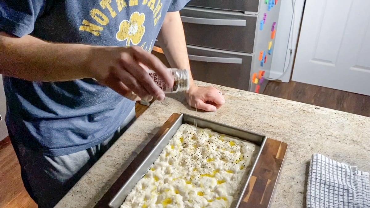 adding toppings to focaccia dough