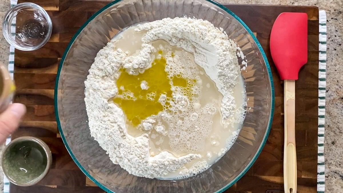 adding olive oil to focaccia dough