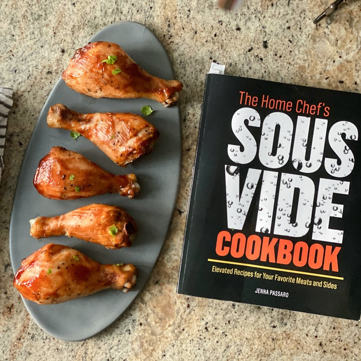 Cooked chicken legs on gray oval plate next to cookbook
