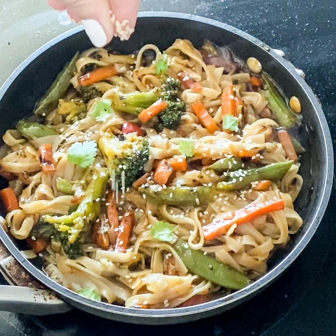 garnishing stir fry with sesame seeds