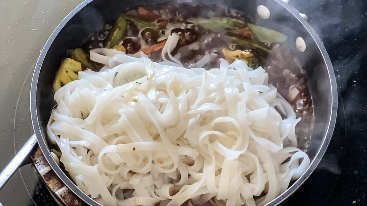adding cooked rice noodles to stir fry