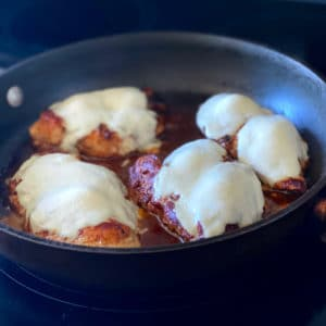 Italian Style Balsamic Marinated Chicken With Mozzarella Baking In A Pan On The Stove