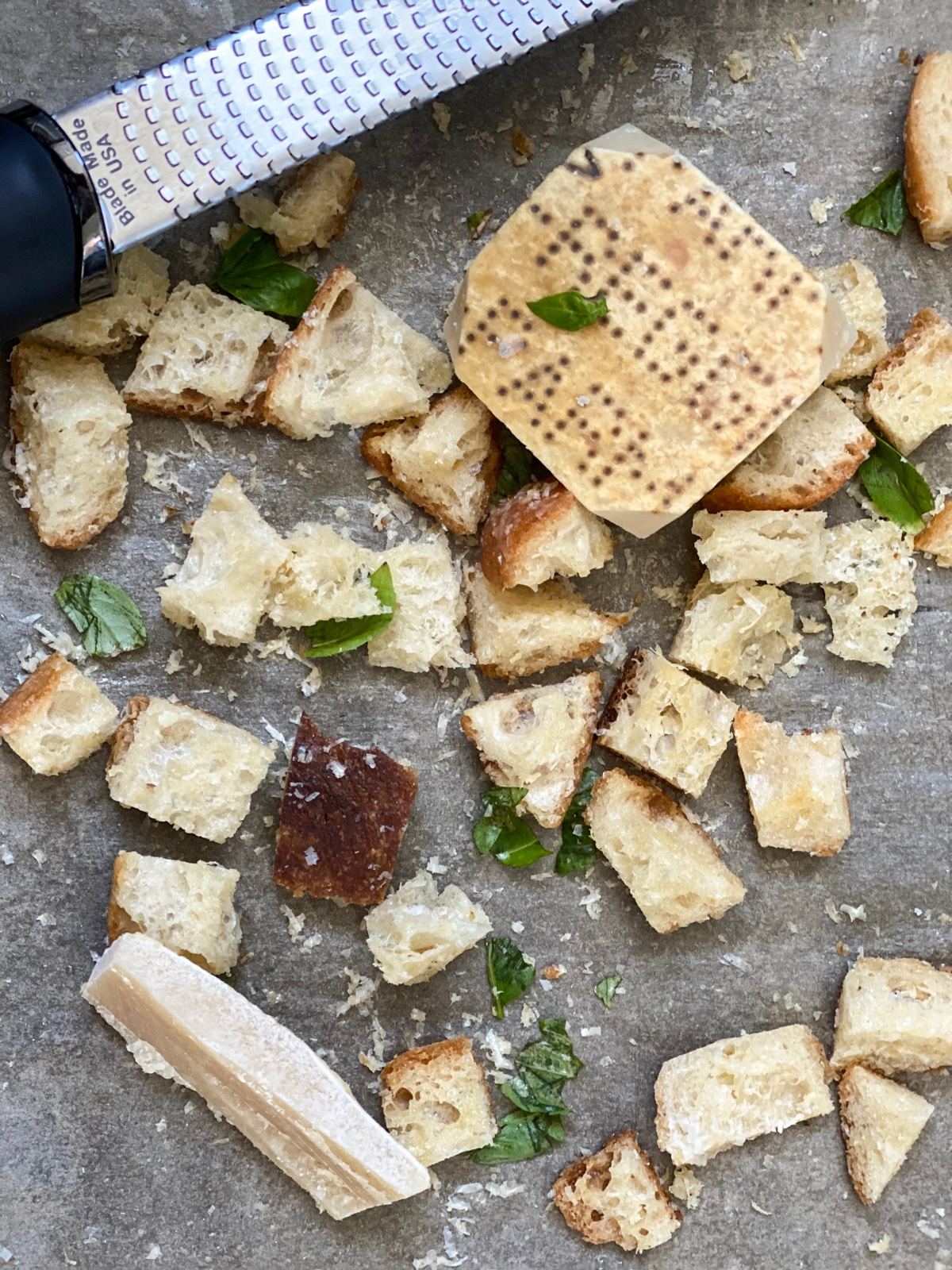 croutons on a baking sheet with parmesan and cheese grater