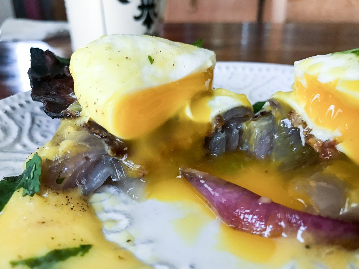 gooey sous vide poached egg with hollandaise sauce on red onion