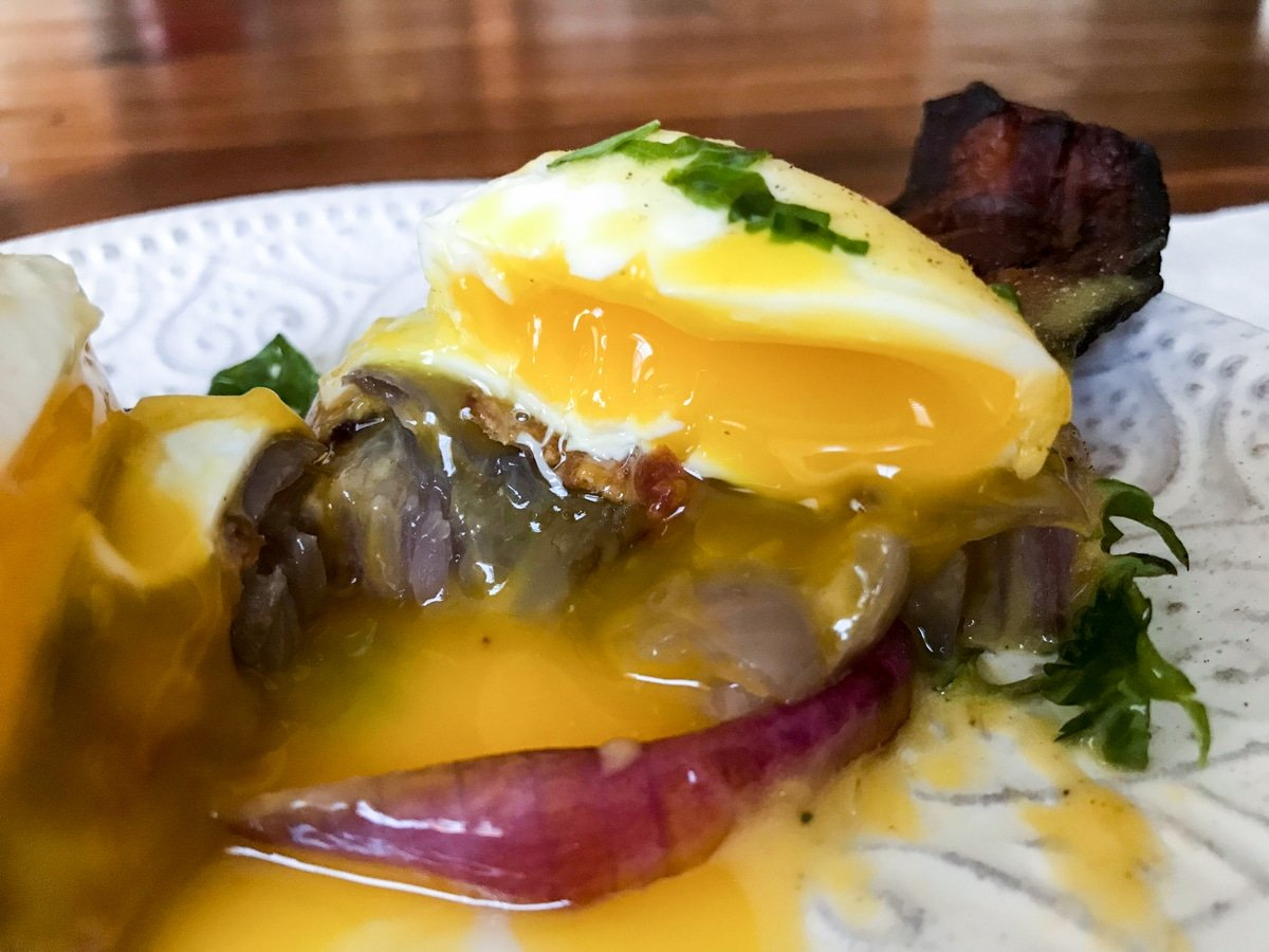 perfectly cooked sous vide poached eggs and hollandaise sauce on grilled onion