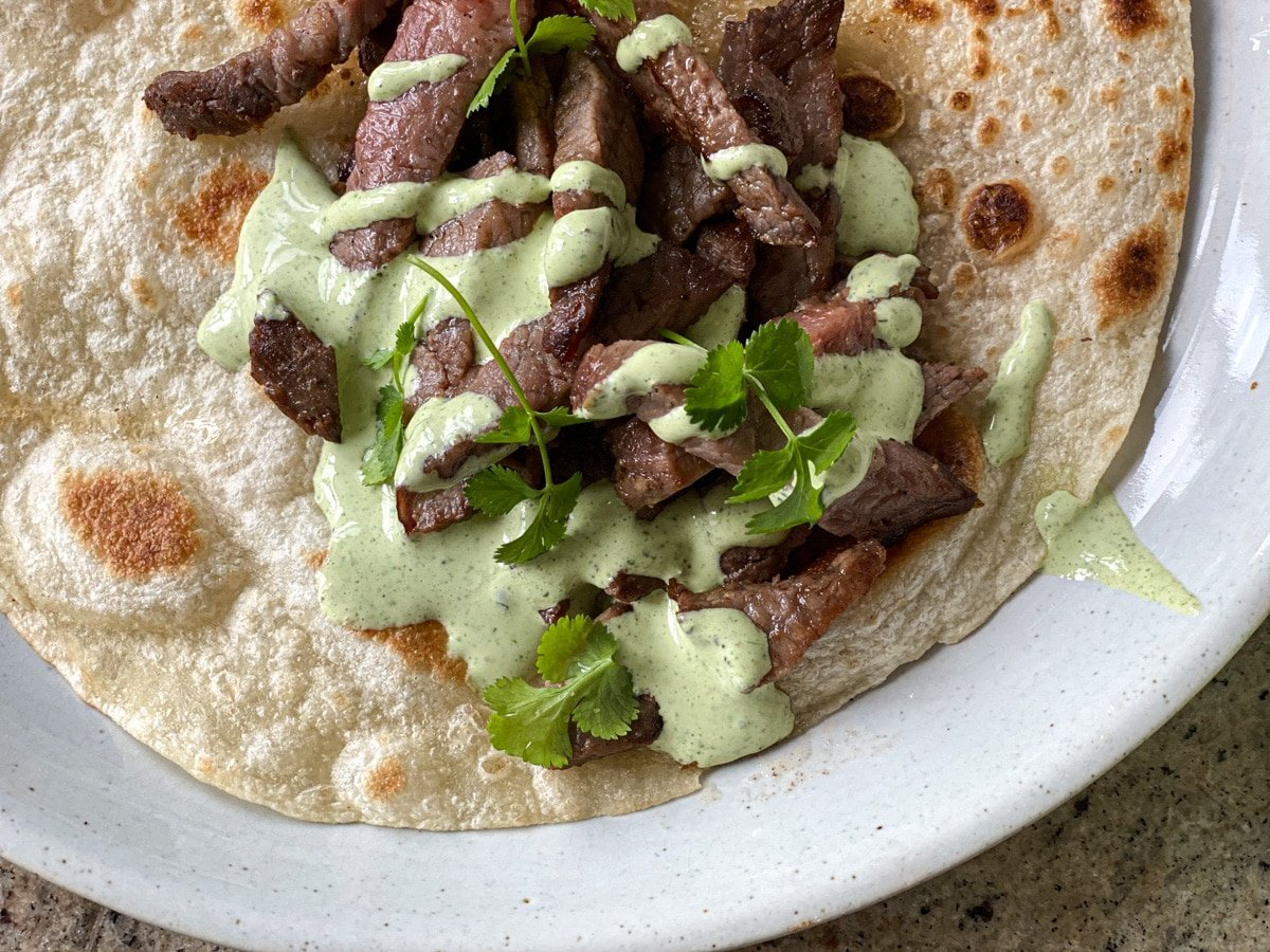 creamy jalapeno ranch sauce on steak tacos with cilantro