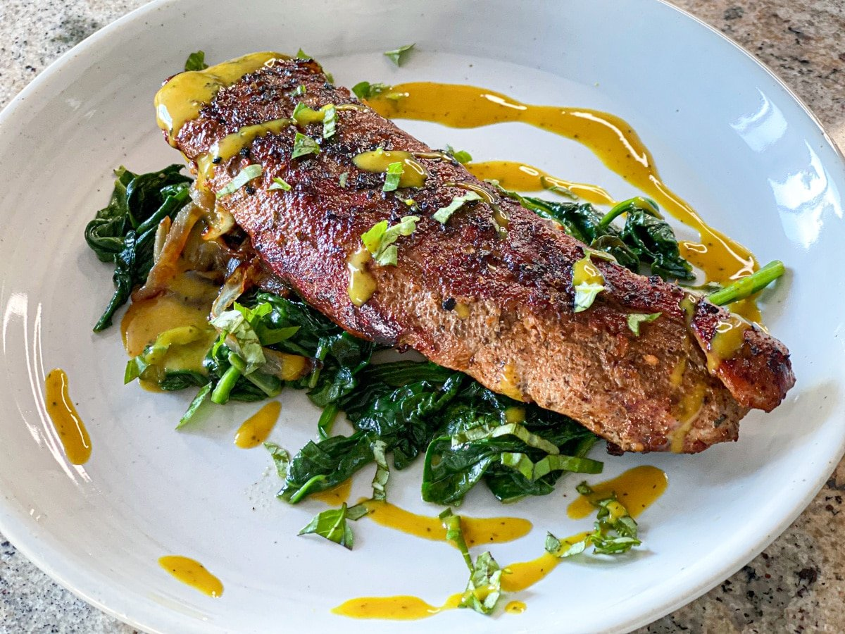 sous vide pork tenderloin recipe plated with yellow bbq sauce and spinach