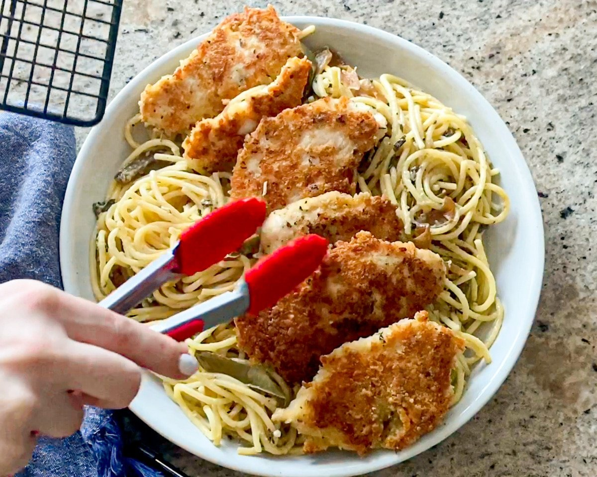 adding chicken to alfredo pasta dish